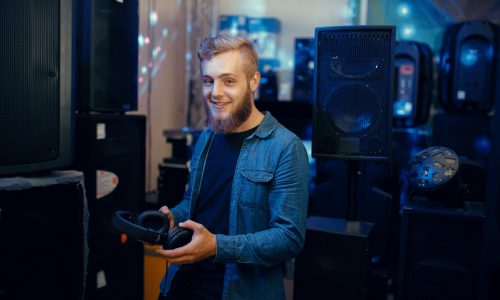 Young musician choosing headphones in music store